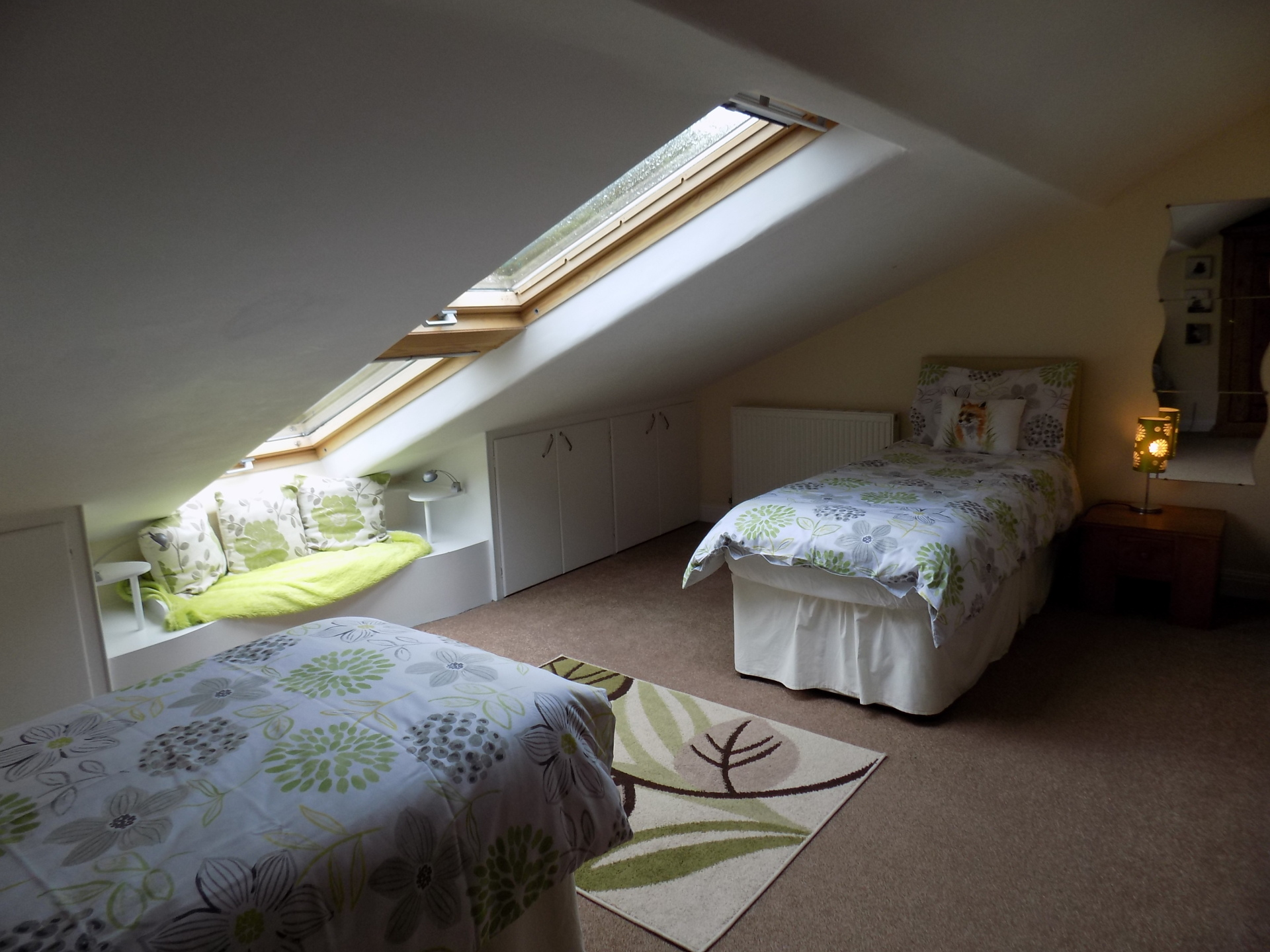 Twin bedroom with sloping ceiling and field views.