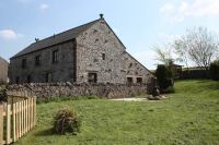 Large detached stone barn conversion with garden and pond.