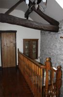 Landing with stone walls leading to bedrooms and bathroom.