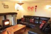 Living room / lounge with leather sofas, log burner and television.